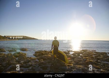 Homme debout avec Paddleboard sur côte rocheuse, vue arrière, Florida Keys, USA Banque D'Images