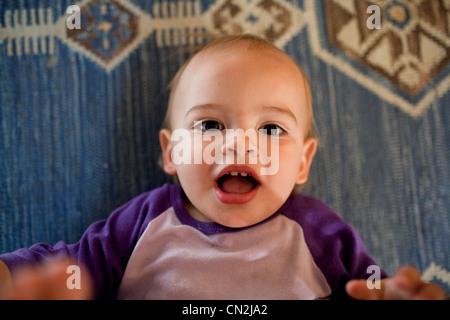 Bébé garçon couché sur un tapis sur le plancher Banque D'Images