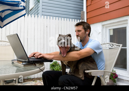 Man with dog sitting on lap Banque D'Images