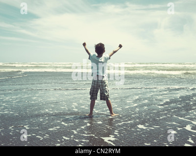 Je retiens la mer: boy on beach, en Nouvelle-Zélande. Banque D'Images