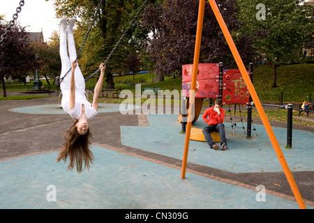 Teenage girl on swing en aire de jeux, à l'envers Banque D'Images