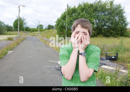 Teenage boy couvrant le visage avec les mains Banque D'Images