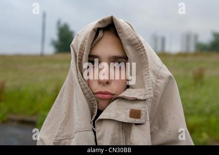 Triste à la Teenage girl with coat couvrant head Banque D'Images