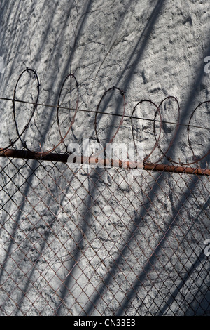 Barbelés et mur avec ombre Banque D'Images