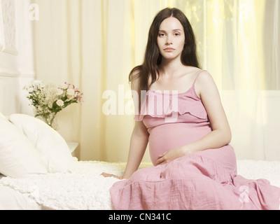 Portrait d'une jeune femme enceinte à la fenêtre Banque D'Images