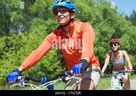 Portrait of a handsome man riding a bike avec son épouse sur l'arrière-plan Banque D'Images