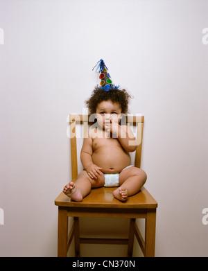 Bébé garçon assis sur une chaise dans un party hat et ramasser son nez Banque D'Images