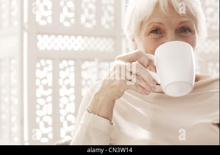 Senior woman drinking coffee, portrait Banque D'Images