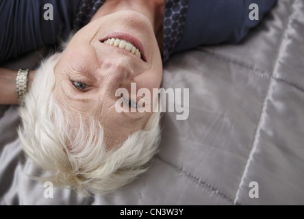 Senior woman relaxing on bed, smiling Banque D'Images