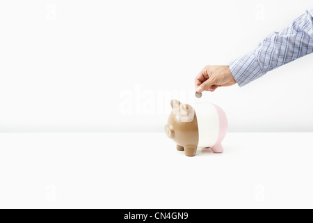 Man putting coins in piggy bank Banque D'Images