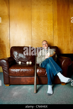 Senior man sitting on couch with baseball bat Banque D'Images