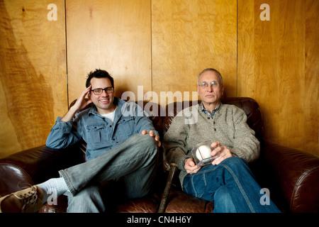 Père et fils adulte sitting on couch, smiling Banque D'Images