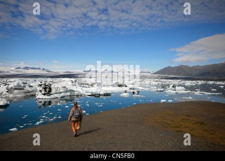 L'Islande, Région de l'Austurland Walker, en face de la lac glaciaire Jökulsárlón et son glacier Breidamerkurjokull Banque D'Images