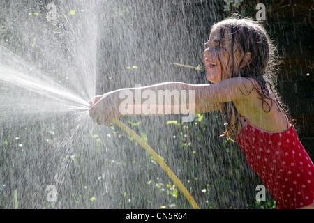 Fillette de six ans avec un tuyau d'arrosage pulvériser de l'eau Banque D'Images