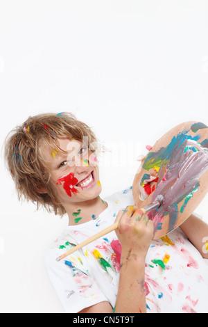 Cheeky kid jouer avec Paint Banque D'Images