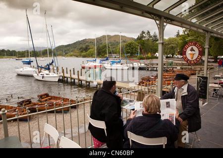 UK, Cumbria, Ambleside, les visiteurs assis dans un café de lire les journaux à côté du lac de Windermere Banque D'Images