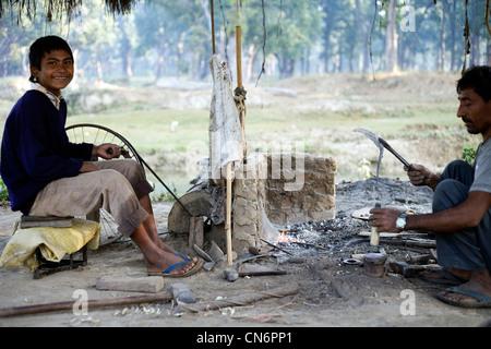 Forgeron de village travaillant avec son fils à Bardia National Park Banque D'Images