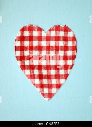 Un cœur rouge et blanc sur un fond bleu clair Banque D'Images