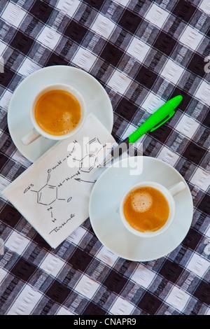 Vue de dessus de café dans des tasses avec symboles chimiques sur une serviette Banque D'Images
