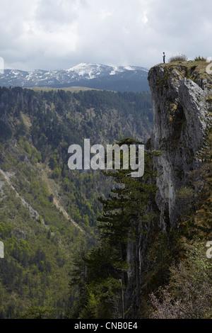 Homme debout sur une falaise rocheuse Banque D'Images