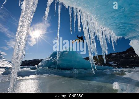COMPOSITE: soleil brille à travers les glaçons suspendus à un iceberg qu'un grimpeur sur glace rappels sur le bord, Banque D'Images