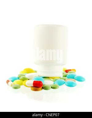 Bouteille avec une chute de nombreux comprimés de couleur sur fond blanc Banque D'Images