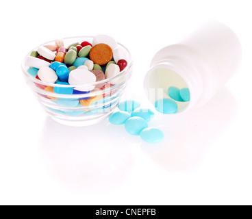 Flacon blanc bleu transparent avec des comprimés et soucoupe avec de nombreux comprimés de couleur Banque D'Images