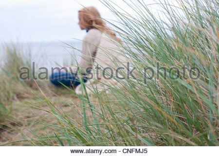 Teenage girl sitting in grass on beach Banque D'Images