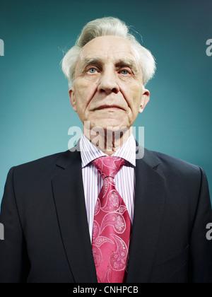 Un élégant hauts homme portant un costume et cravate rose vif Banque D'Images