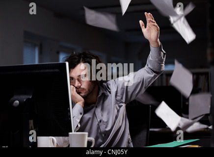 Employée de bureau travaillant tard, jeter le papier dans l'air Banque D'Images