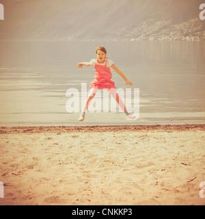Fille saute en l'air sur une plage Banque D'Images