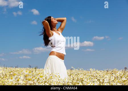 Jeune femme en blanc au milieu d'une journée ensoleillée sur camomille