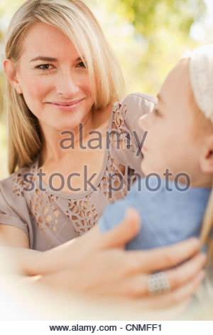 Smiling mother holding daughter outdoors Banque D'Images