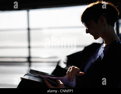 Woman Reading magazine in airport Banque D'Images