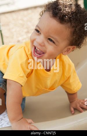 Portrait de jeune garçon grimper Diapositive dans Jeux pour Enfants Banque D'Images