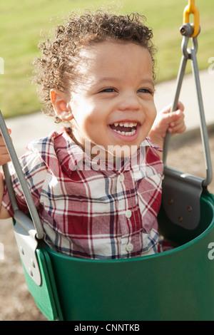 Close-up Portrait of Young Boy in Swing à l'aire de jeux Banque D'Images