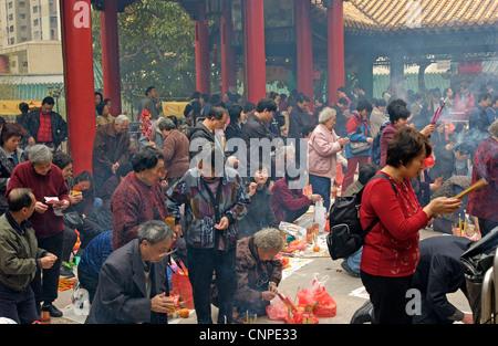 Les fidèles des la Sik Sik Yuen Wong Tai Sin Temple Hong Kong le culte de la lumière sur l'autel des bâtons avant Banque D'Images