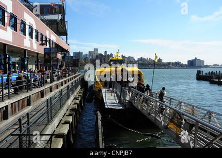 Vue sur le ciel bleu, vers Brooklyn skyline, bateau-taxi jaune amarré aux côtés de la rivière East Pier 17, South Street Seaport, New York