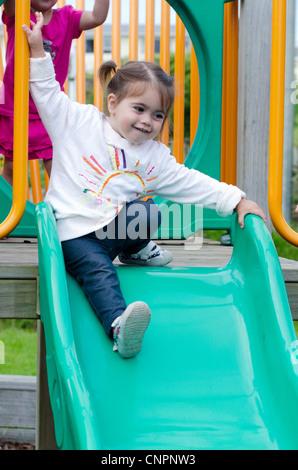 Un enfant de 2 ans glisse en bas une diapositive et joue dans une aire de jeux. Banque D'Images