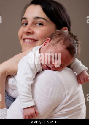 Mère portant l'enfant endormi Banque D'Images