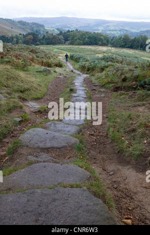 Petite figure la marche sur sentier en pierre de granit en descendant de Stanage Edge, Derbyshire, Dark Peak, Peak Banque D'Images