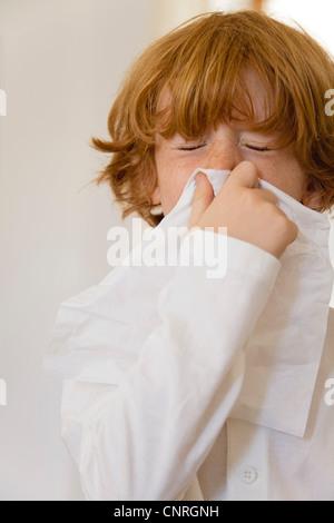 Boy blowing nose sur le tissu avec les yeux fermés Banque D'Images