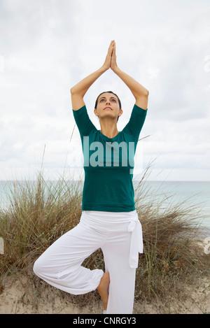 Femme mature en posture de l'arbre sur la plage, portrait Banque D'Images
