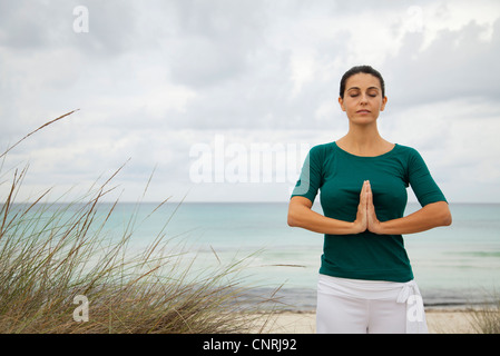 Femme mature en position de prière sur la plage, portrait