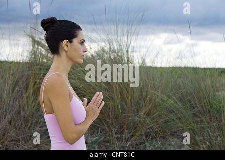 Femme mature en position de prière en plein air, side view