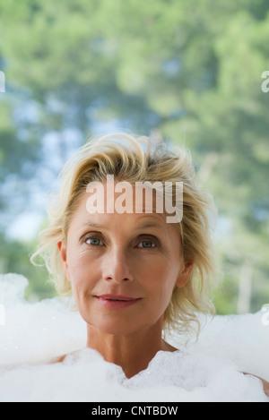 Young woman in bubble bath, portrait Banque D'Images
