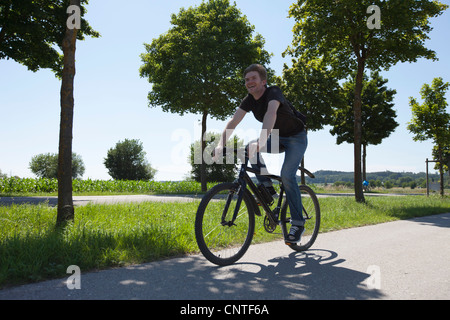 Man riding bicycle on rural road Banque D'Images