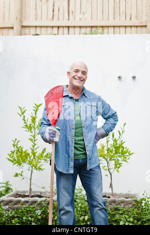 Older Man holding rake in backyard Banque D'Images