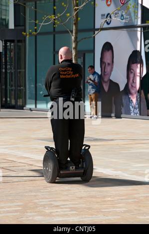 Garde de sécurité sur un transporteur personnel Segway à MediaCityUK, Salford Quays, Manchester, Angleterre, RU Banque D'Images