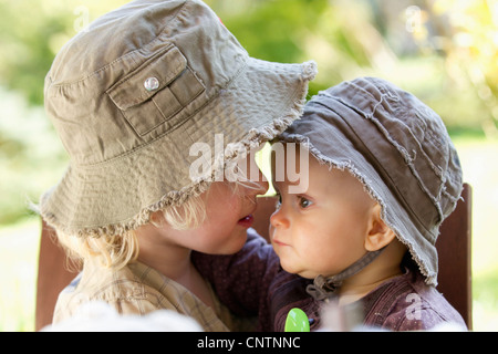 Boy holding baby sister in chair Banque D'Images